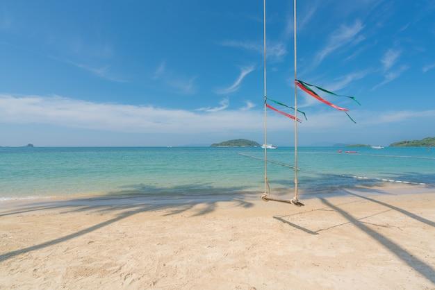 Schwingen sie fall von der kokosnusspalme über sommerstrand mit klarem wassermeer und welle mit schnellboot in phuket, thailand. sommer-, reise-, ferien- und feiertagskonzept.