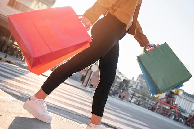 Schwingende einkaufstaschen der jungen dame auf straße