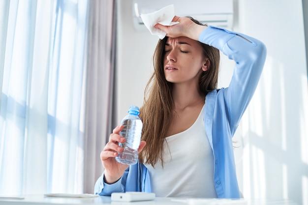 Schwitzende frau, die unter hitze und durst leidet, kühlt mit klimaanlage und erfrischender wasserflasche am heißen sommertag ab