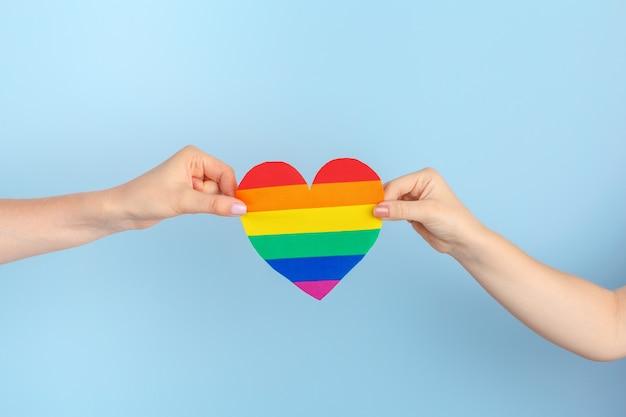 Schwule liebe. menschliche hand, die ein regenbogenpapierherz hält
