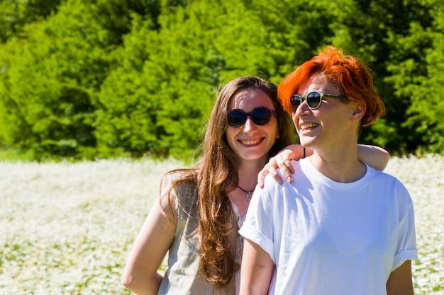 Schwules lesbisches paarporträt, zwei erwachsene frauen im feld von gänseblümchen, lächelnd und umarmt