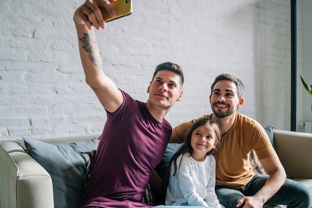 Schwules paar macht ein selfie mit ihrer tochter, während sie zu hause auf einer couch sitzt. familienkonzept.