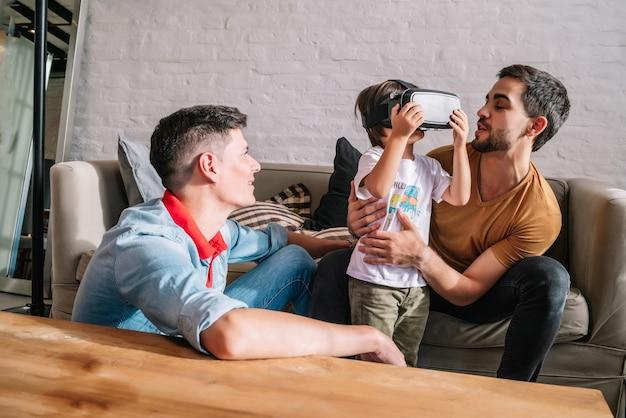 Schwules paar und ihre kinder spielen zu hause zusammen videospiele mit vr-brille. familienkonzept.