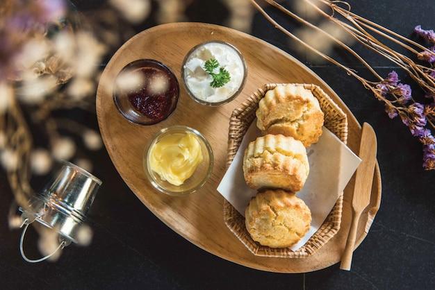Scones mit marmelade und butter mit schlagsahne auf dem tisch.