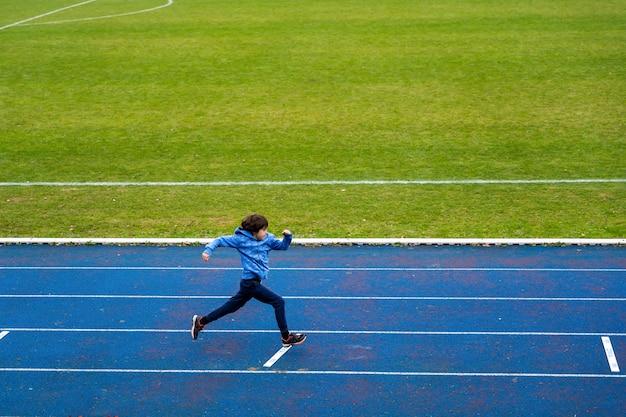 Scooler junge, der draußen läuft. kind macht leichtathletik im stadion. sportkonzept für kinder.