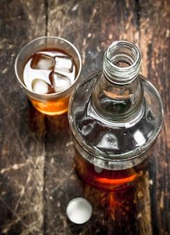 Scotch whisky in der flasche. auf einem hölzernen hintergrund.