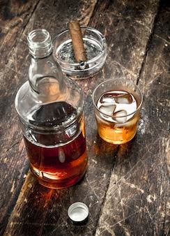 Scotch whisky mit zigarre. auf einem hölzernen hintergrund.