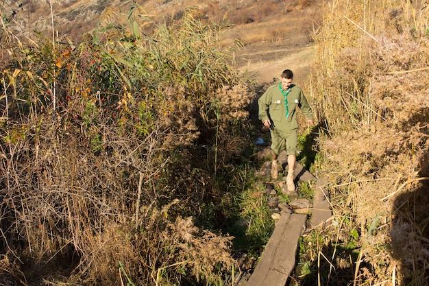 Scout überquert eine schmale fußgängerbrücke aus einem baumstamm über einen bach oder eine schlucht, während er durch die wildnis wandert