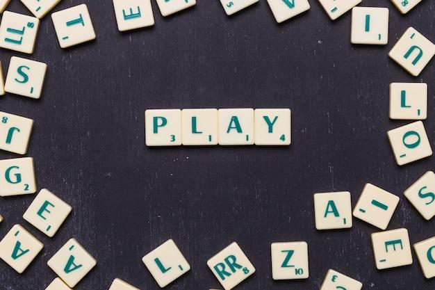 Scrabble-buchstaben über schwarzem hintergrund spielen