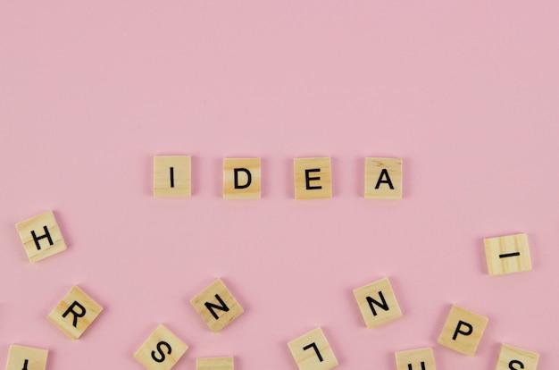 Scrabblebuchstaben und ideenwortkonzept auf rosa hintergrund