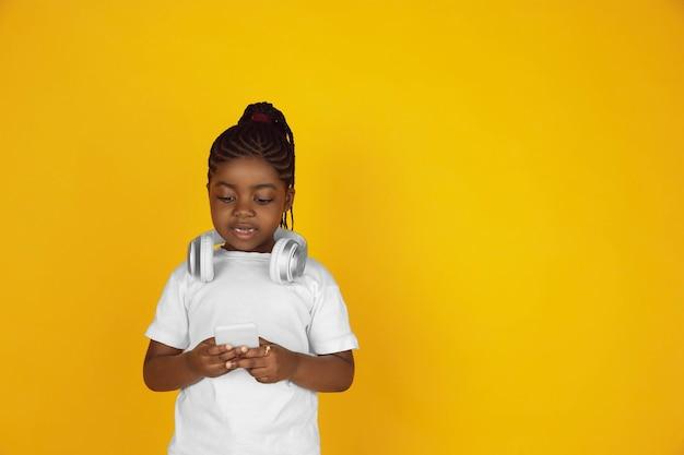 Scrollen des telefons, musik hören. porträt des kleinen afroamerikanischen mädchens auf gelbem studiohintergrund. fröhliches, schönes kind. konzept der menschlichen emotionen, ausdruck, verkauf, anzeige. exemplar. sieht süß aus.