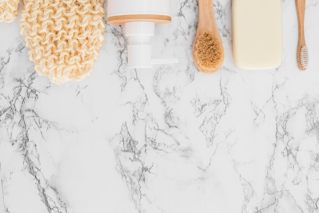 Scrub-handschuh; kosmetische flasche; seife und pinsel auf marmorhintergrund