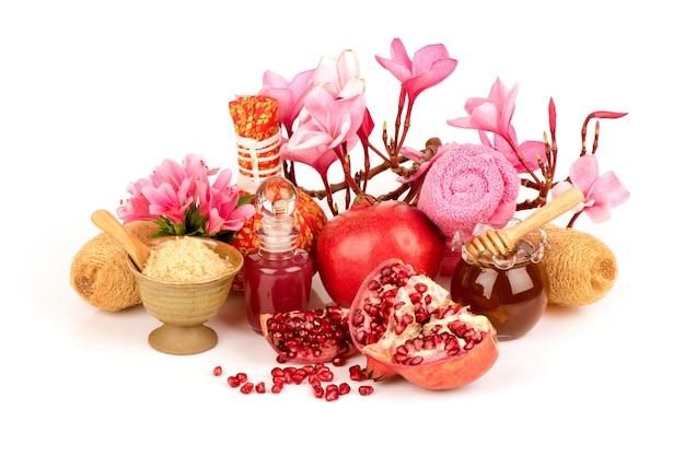 Scrub mit granatapfelfrüchten, honig, rotem zucker lokalisiert auf weißem hintergrund.