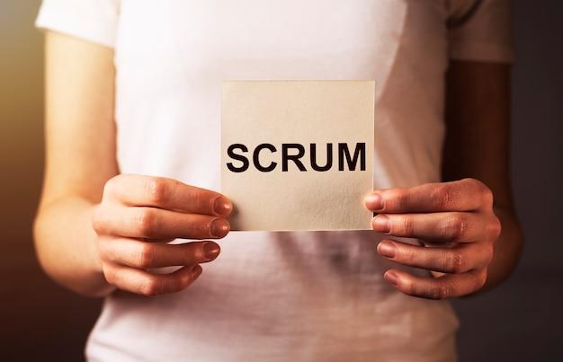 Scrum-wort auf papier in weiblicher handnahaufnahmekonzept von methoden im management