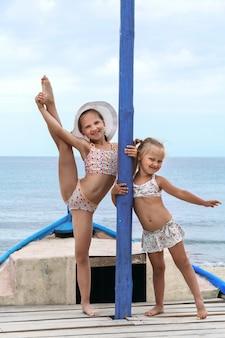 Sea kids urlaub zwei kleine mädchen in badebekleidung stehen im boot auf sand vor meereshintergrund