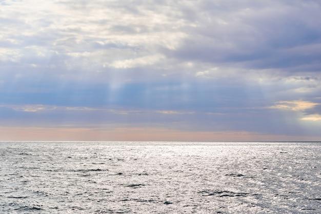 Seascape - die sonnenstrahlen scheinen auf das wintermeer unter bewölktem himmel