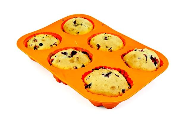 Sechs cupcakes mit beeren in oranger silikonform isoliert