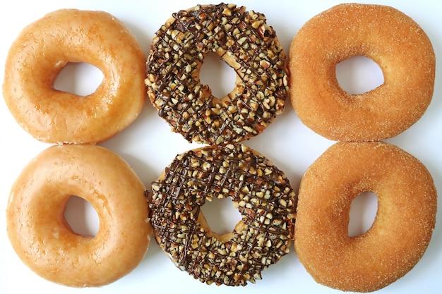 Sechs donuts, zwei zuckerglasiert, zwei schokolade mit nüssen und zwei zimtzucker