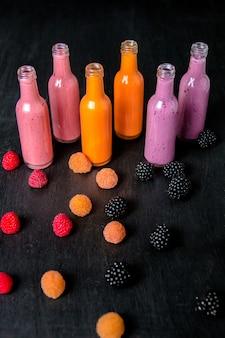 Sechs flaschen mit smoothies und himbeeren (rot, gelb, brombeere) auf schwarz. milchshake glas mit beeren. diät oder veganes essen, frisches vitamin.