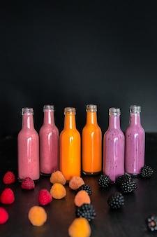 Sechs flaschen mit smoothies und himbeeren (rot, gelb, brombeere) auf schwarz. milchshake im glas mit beeren. diät oder veganes essen, frisches vitamin.