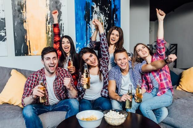 Sechs freunde verbringen ihr wochenende zusammen auf dem sofa, essen popcorn und lachen über eine äußerst amüsante tv-show.