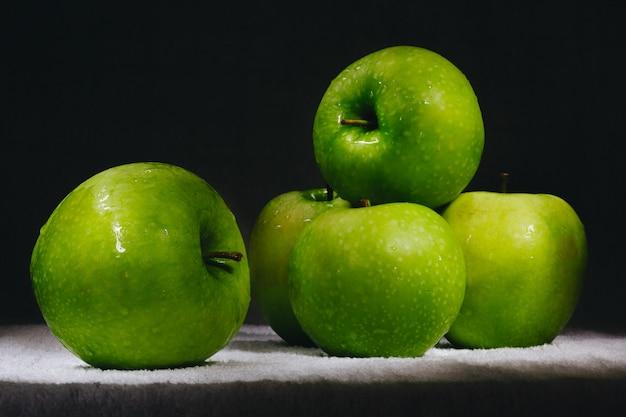 Sechs frische grüne äpfel auf einem dunklen hintergrund