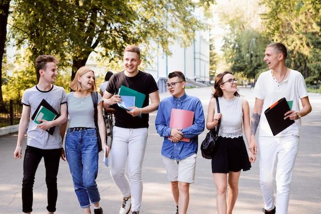 Sechs fröhliche freunde, die nach dem unterricht auf dem studentencampus spazieren gehen