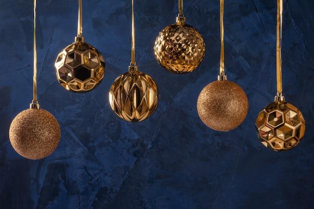Sechs goldene weihnachtskugeln auf blauem hintergrund. kugeln hängen, unterer exemplarplatz. festliches layout.