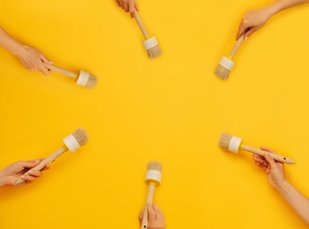 Sechs hände, die pinsel auf gelbem hintergrund mit kopienraumkonzept der kreativität halten