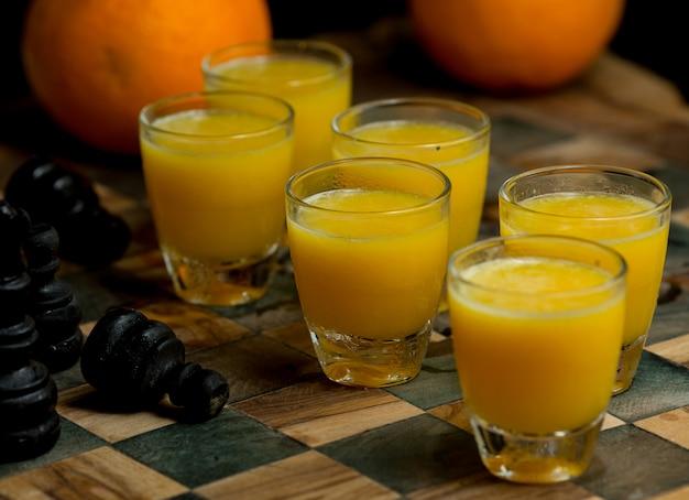 Sechs kleine gläser frische orangensäfte auf einem scheckkarton