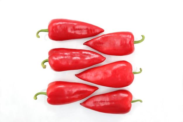 Sechs leuchtend rote paprika auf einem weißen