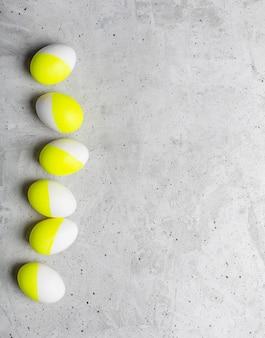 Sechs osterfarbene eier, die auf einem grauen hintergrund liegen
