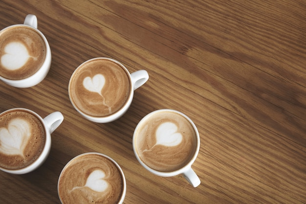 Sechs schöne weiße keramikbecher mit cappuccino isoliert auf holztisch. schaum oben in fliegender herzform