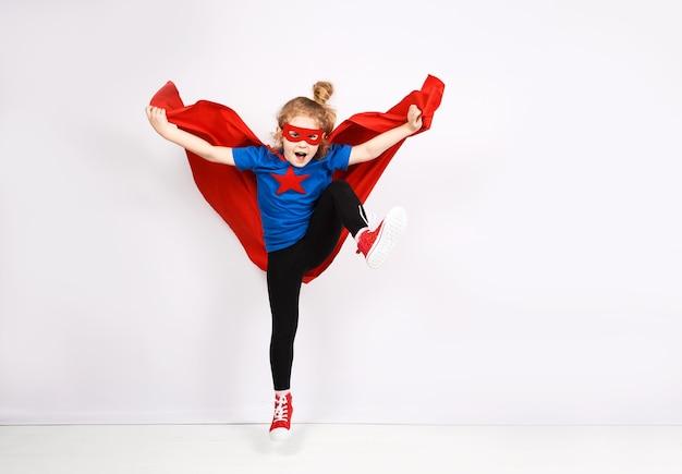 Sechsjähriges blondes mädchen, gekleidet wie superheld, der spaß zu hause hat. weiße wand im hintergrund.