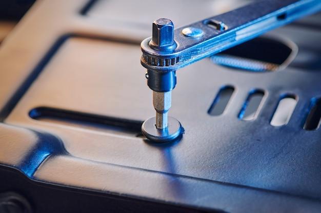 Sechskantschrauben in metallstahlplatte einschrauben. hardware-werkzeuge und metallschrauben. verbindungskonzept und waren zur reparatur.