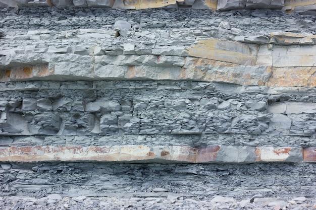 Sedimentgesteinwand-beschaffenheitshintergrund auf schwarzem meer