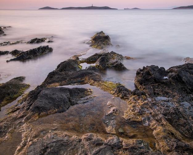 See bedeckt mit felsen und nebel mit hügeln auf dem hintergrund während des sonnenuntergangs