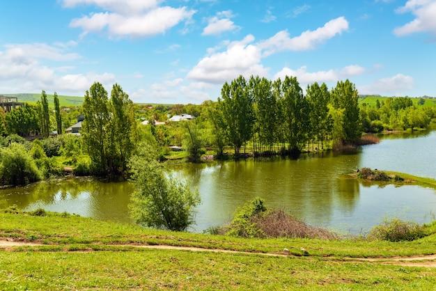 See bei einem dorf mit grünen hügeln