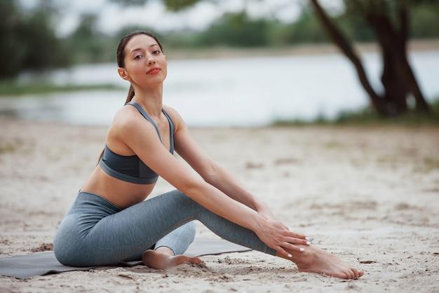 See dahinter. brünette mit schöner körperform in sportlicher kleidung haben fitness-tag am strand
