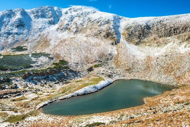 See in der gebirgslandschaft mit schnee und sonnenuntergangszeit