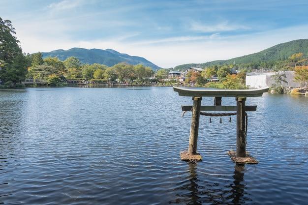 See kinrin und japanisches tor (torii) mit hintergrund des bergs yufu und des blauen himmels bei yufuin, oita, kyushu, japan