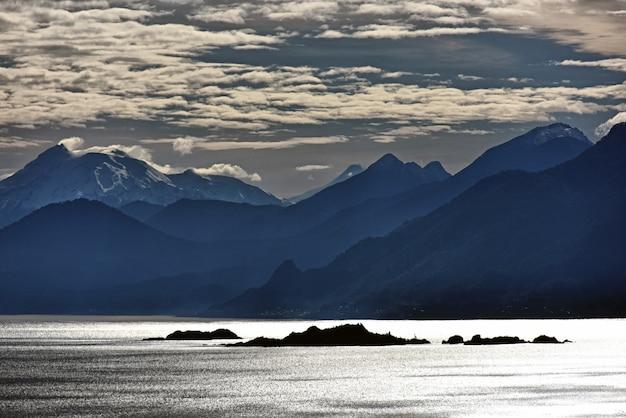 See mit einer reflexion von wolken darauf während der dämmerung