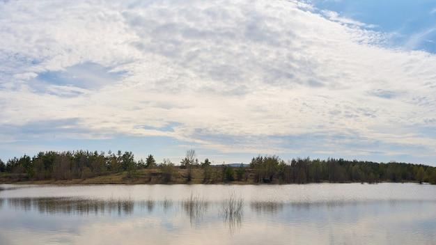 See mit schönen wolken und wald an einem sonnigen tag.