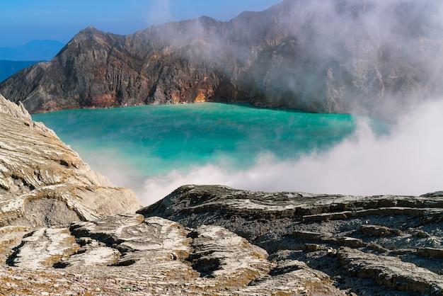 See mitten in einer felsigen landschaft, die rauch ausstößt