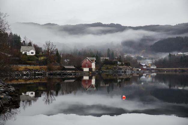 See umgeben von gebäuden mit bergen bedeckt mit wäldern und nebel, der sich auf dem wasser spiegelt