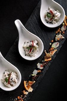 Seebarsch-ceviche-mini-portionen, serviert in wunderschönen chinesischen löffeln