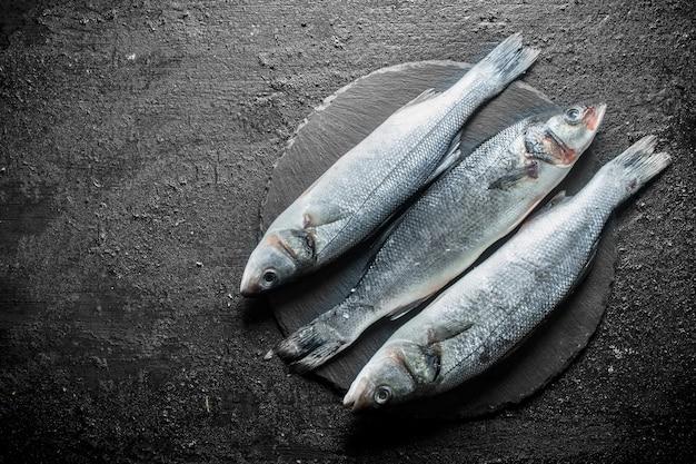 Seebarsch roher fisch. auf schwarzem rustikalem hintergrund