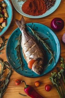 Seebrassenfisch und zutaten zum kochen auf einem tisch