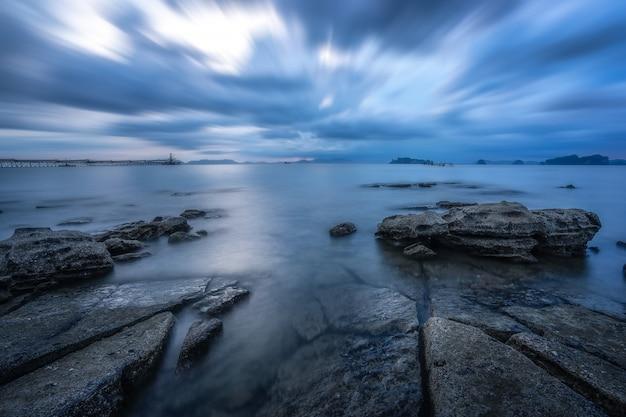 Seefelsen ruhiges meer und leerer strand. am strand mit blauem meeresblauem himmel für ferien.