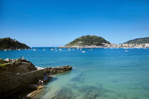 Seehafen in der stadt san sebastian, spanien. felsiges ufer mit blick auf den golf von biskaya und die inseln